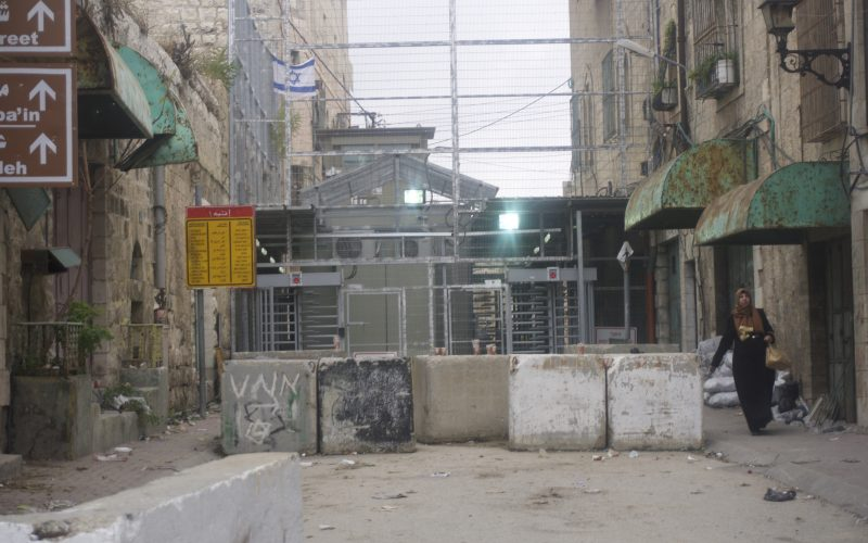 Palestinian woman walking out of the Israeli checkpoint and in to the H2 zone, Hebron. December 11, 2016. Photo: Masih Sadat