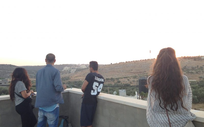 Standing on top of the roof of a house in Bil'in with the separation barrier in the background. August 20, 2014. Photo: Masih Sadat