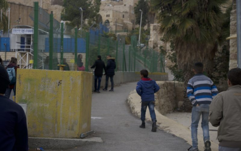 In Hebron/Al-Khalil, Palestinians walking on the site of the road specifically for Arabs and Muslims while Jews and non-Muslims walk on the other side. December 11, 2016. Photo: Masih Sadat